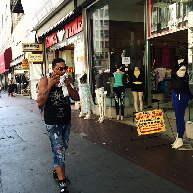 """In downtown LA, a man bites into a delicious looking burrito as he strolls down a street of shops on Broadway."" @americanobs…"